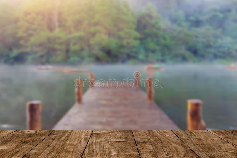 木桌有迷离木桥梁船坞湖旅行背景 免版税库存照片