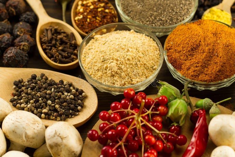 木桌用五颜六色的香料、草本和菜 免版税库存照片