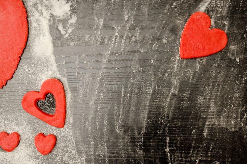 黑木桌用面粉,红色心脏由面团制成在框架的边缘附近 顶视图,文本的空间 库存图片