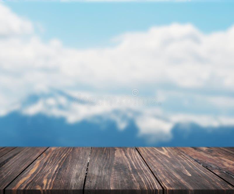 木桌的图象在摘要前面的弄脏了山背景  可以为显示或蒙太奇使用您的产品 嘲笑 库存照片