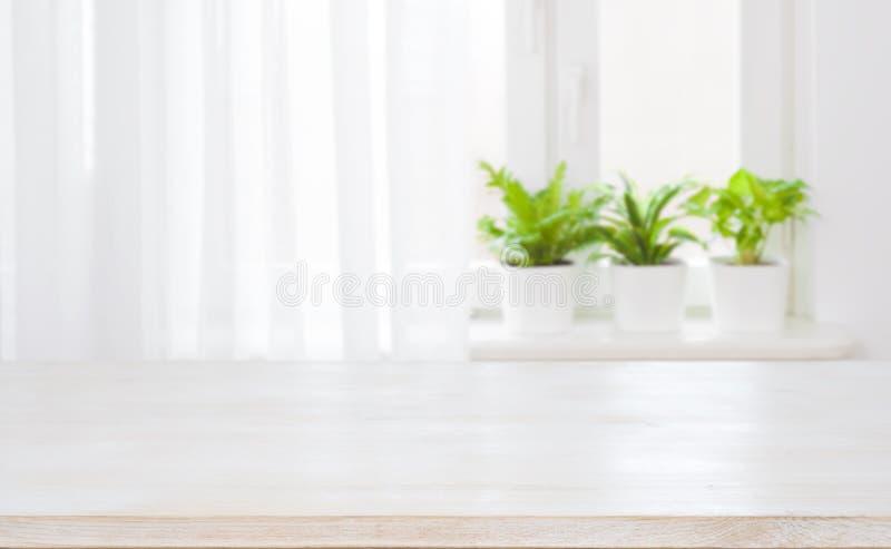 木桌空的上面在被弄脏的curtained窗口背景的 库存图片
