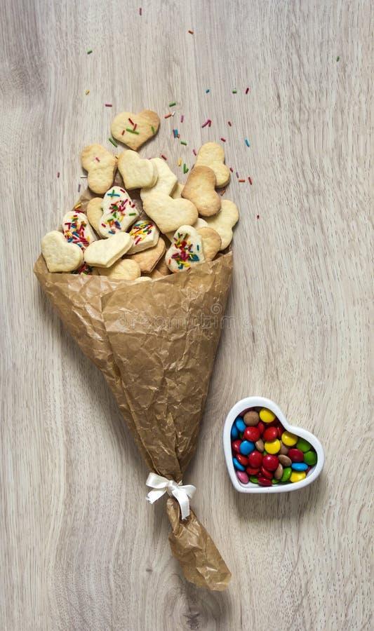 木桌说谎堆与曲奇饼形式心脏的被弄皱的纸和一个搽粉的多彩多姿的心脏花瓶用五颜六色的糖果 免版税库存图片
