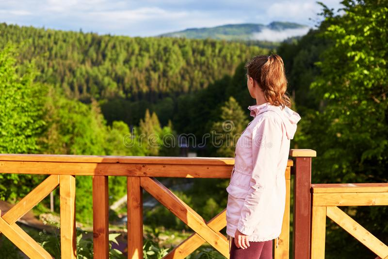 木桥室外射击或阳台在山边,绿色森林和晴朗的小山,年轻微小的妇女身分外形, 免版税库存图片