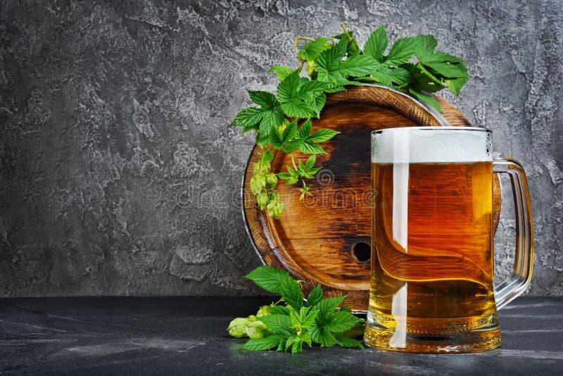 木桶与玻璃杯子和蛇麻草的工艺啤酒在黑暗的地窖里 免版税库存照片