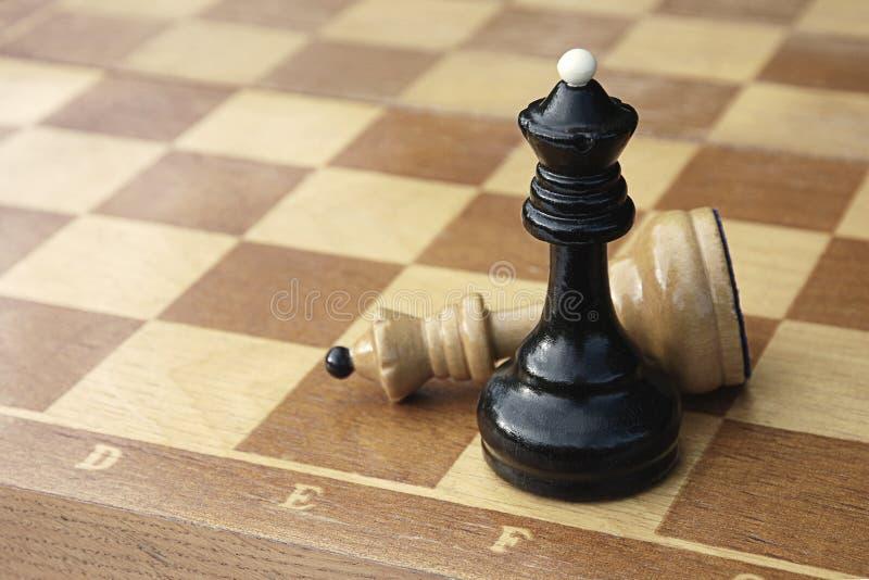 木棋盘的两位棋国王 白色图在黑人优胜者旁边被击败的说谎 免版税库存图片