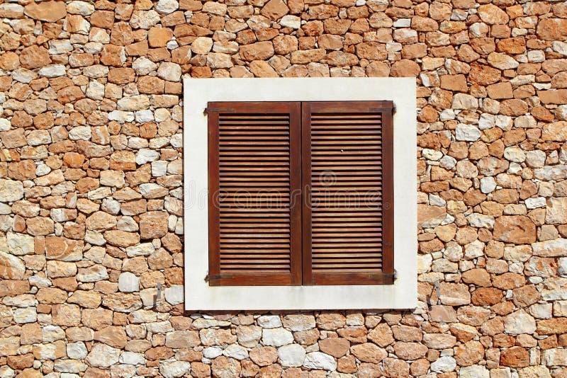 木棕色石造壁的视窗 免版税库存照片