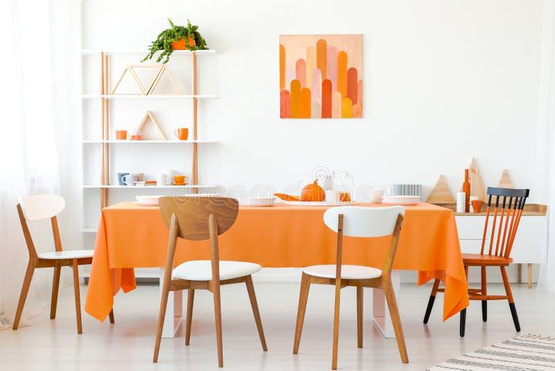 木椅子在橙色桌上在白色餐厅 图库摄影