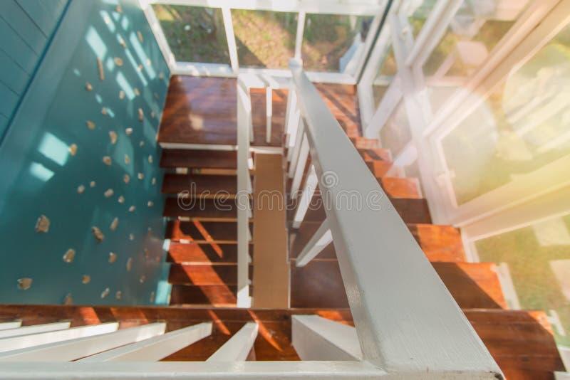 木楼梯在现代家 房子的边是玻璃与蓝色墙壁 免版税库存图片