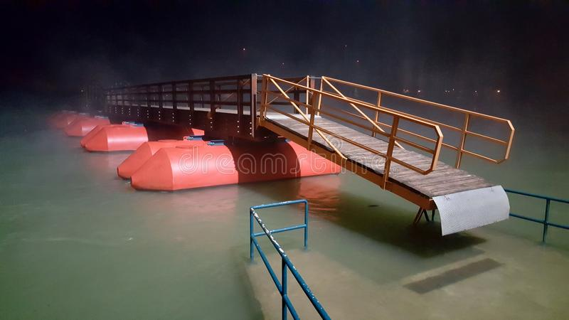 木浮方船桥梁围拢与雾在晚上在洪水期间 免版税库存图片