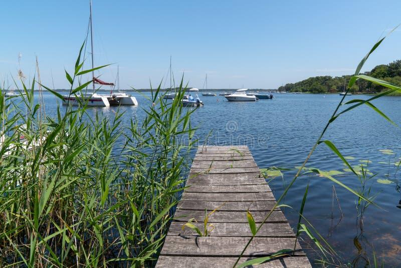 木浮船在有小船的Lacanau湖在法国 免版税库存图片