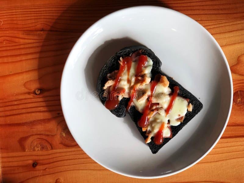 木炭面包做的微型薄饼冠上了用烟肉和乳酪 免版税库存图片