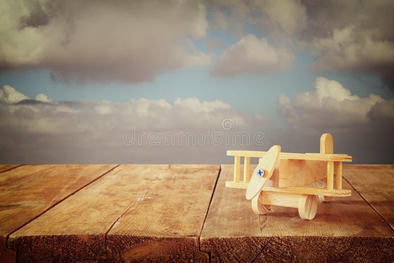 木玩具飞机的图象在木桌的反对多云天空 棒图象夫人减速火箭的抽烟的样式 库存照片