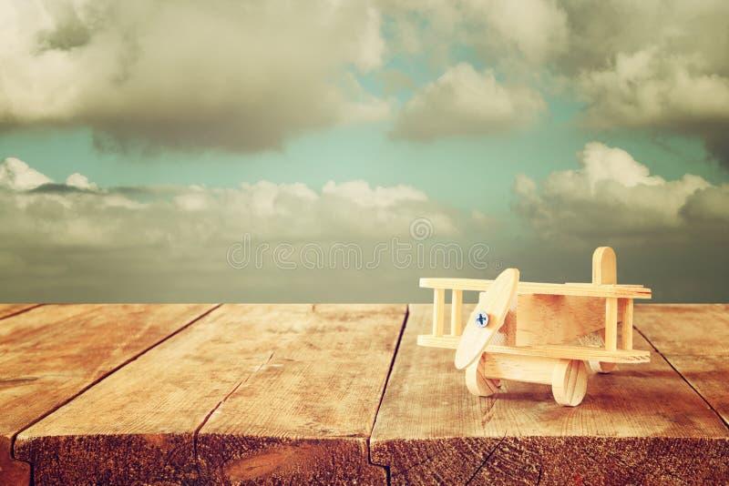 木玩具飞机的图象在木桌的反对多云天空 棒图象夫人减速火箭的抽烟的样式 免版税库存图片