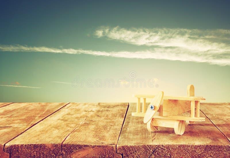 木玩具飞机的图象在木桌的反对日落天空 棒图象夫人减速火箭的抽烟的样式 免版税库存照片