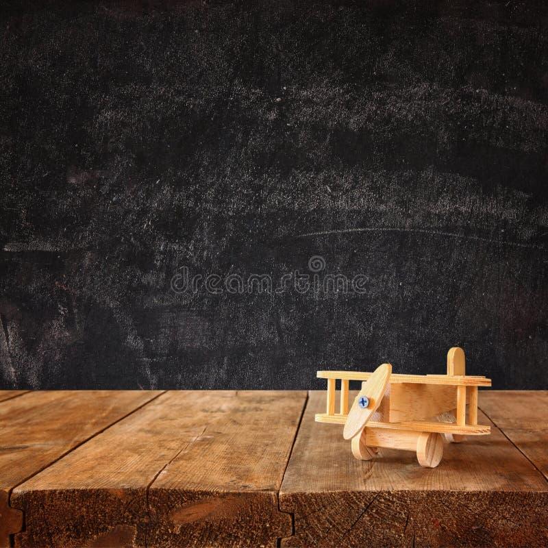 木玩具飞机的图象在木桌的反对白垩黑板背景 棒图象夫人减速火箭的抽烟的样式 免版税库存图片