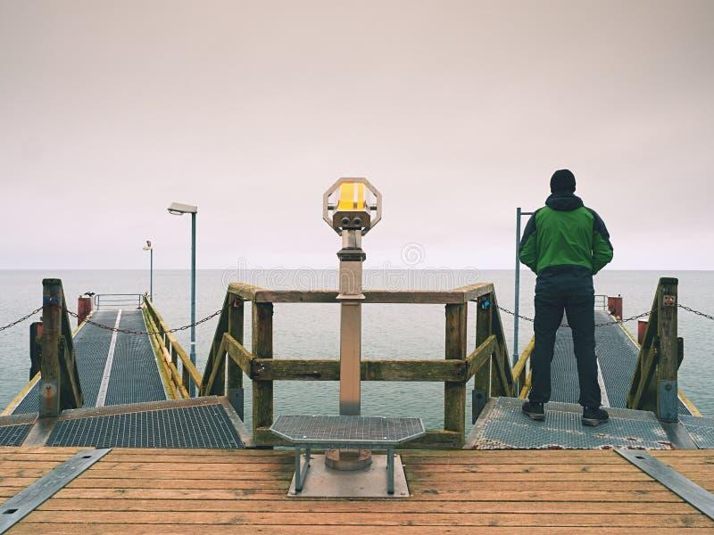 木痣的人在港口在秋天有薄雾的天之内 扶手栏杆的游人 免版税库存照片