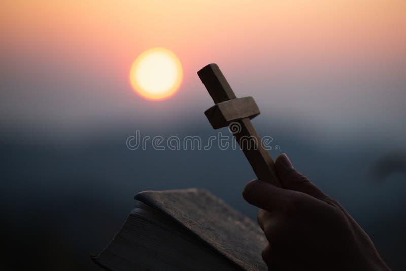 木的手对负横渡在山背景的开放圣经与早晨日出、spirtuality和宗教, 库存图片