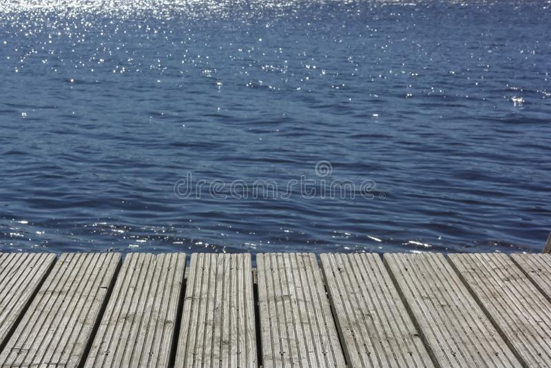 木码头的田园诗看法在停泊表面反射镜天空的湖或河 库存照片