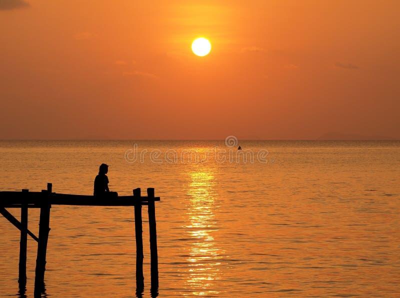 木码头的凝思人在日落天空下 库存图片