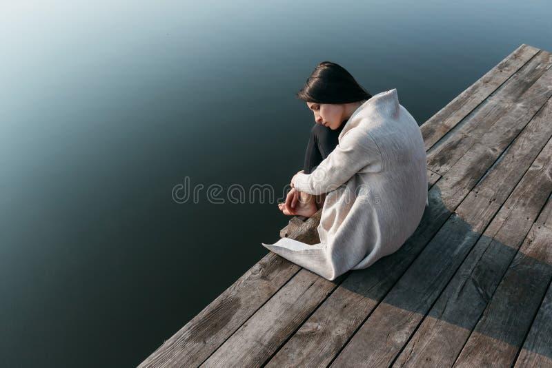 木码头的美丽的女孩在水附近 免版税库存图片