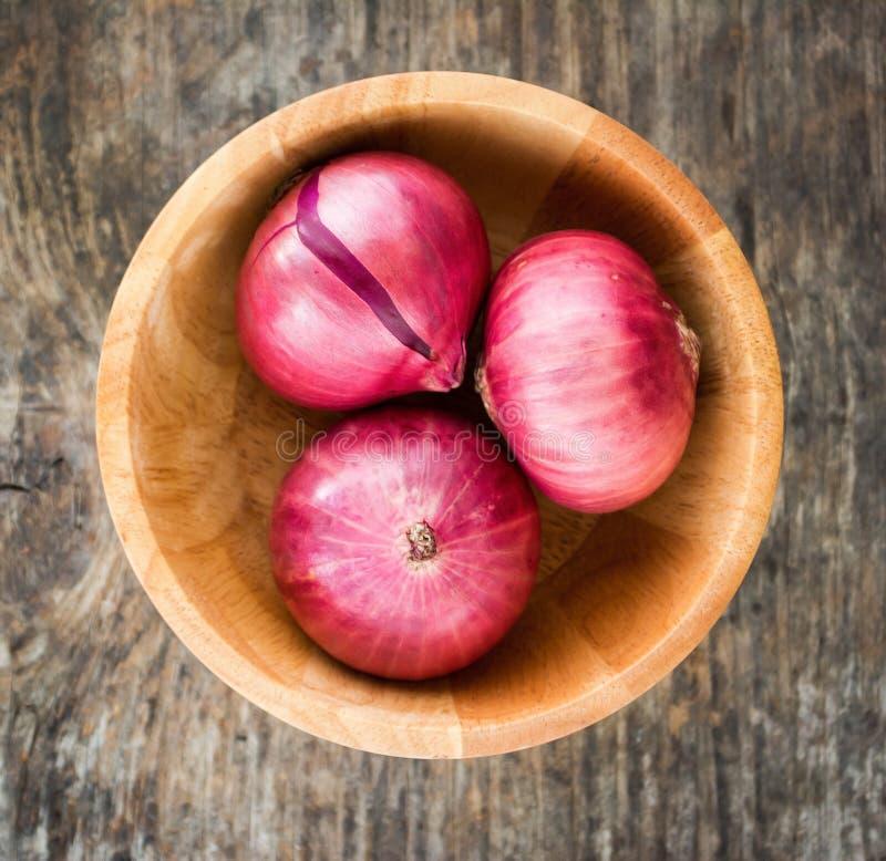 木碗用在老木背景的红洋葱 库存图片