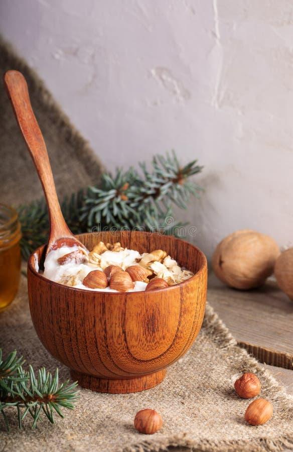 木碗酸奶用燕麦片和坚果和站立匙子在粗麻布在白色墙壁背景 库存照片