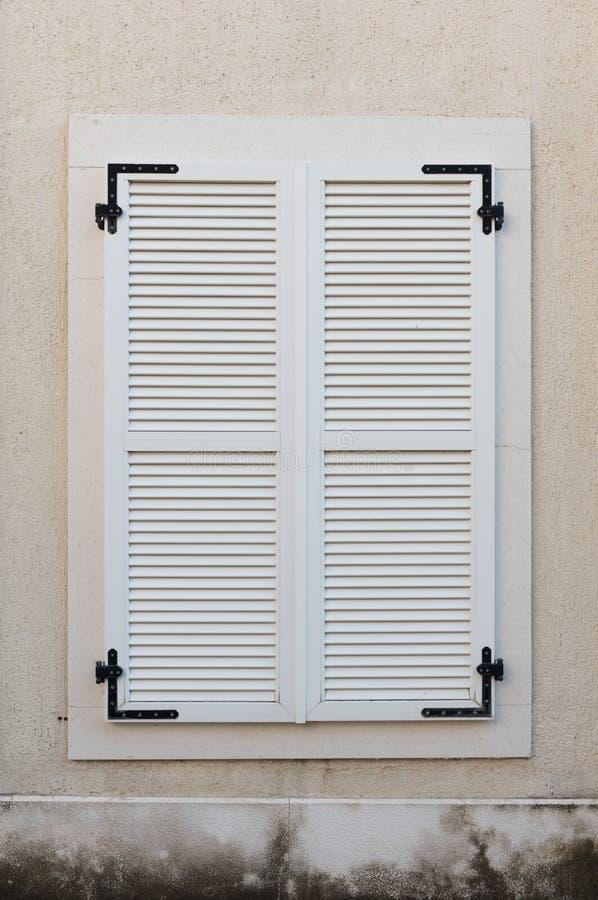 木窗口关上与白色木快门 外部房子细节 库存照片