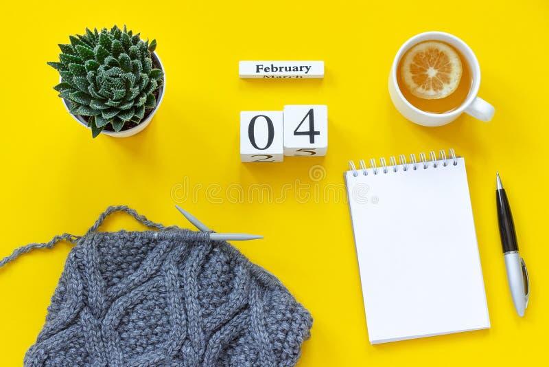 木立方体日历2月4日 茶用柠檬,文本的空的开放笔记薄 有多汁和灰色织品的罐 库存照片