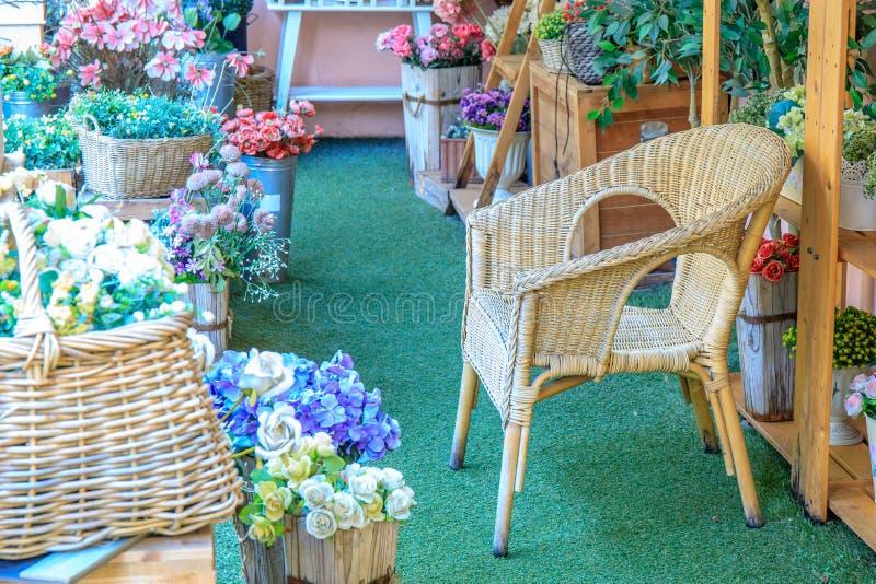 木竹椅子在房子或家里有五颜六色的美丽的假花的 库存照片