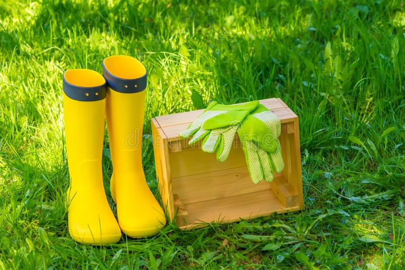 木箱、绿色手套和黄色胶靴在豪华的草在后院 免版税库存图片