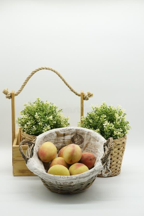 木篮子用在白色背景的桃子 免版税库存照片