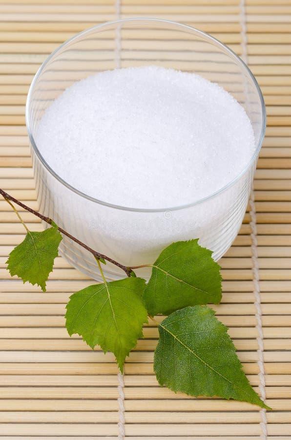 木糖醇在玻璃碗的桦树糖有桦树的在竹席子离开 库存图片