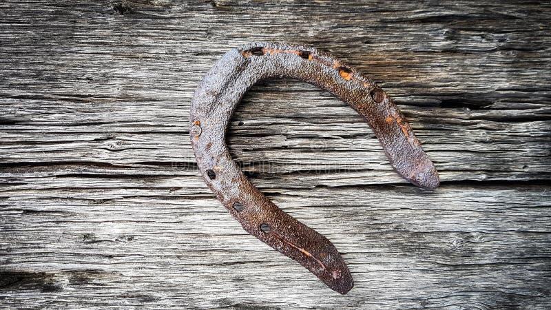木纹理表面上别住和钉牢的爆发的老生锈的金属马掌 免版税库存图片