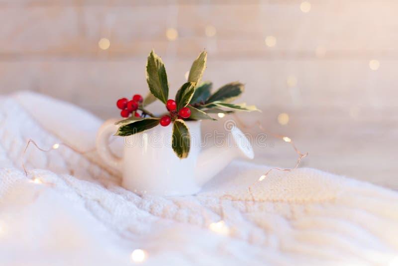 木织背景上白水壶中红莓冬青枝 库存图片