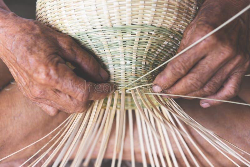 木编织的竹的篮子-老自然产品的老人手运作的工艺手工制造篮子在亚洲 免版税库存照片
