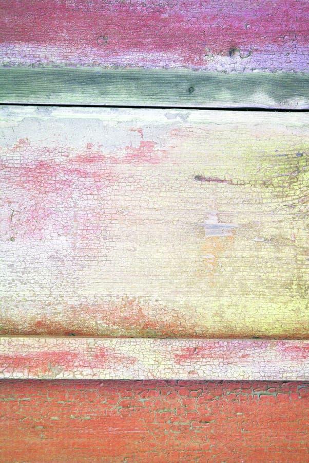 木老表面绘与紫色,绿色和红色破旧的油漆,垂直的难看的东西背景 免版税库存图片