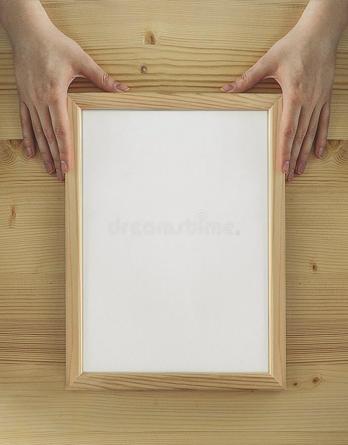 木背景妇女手中的木框 免版税库存照片