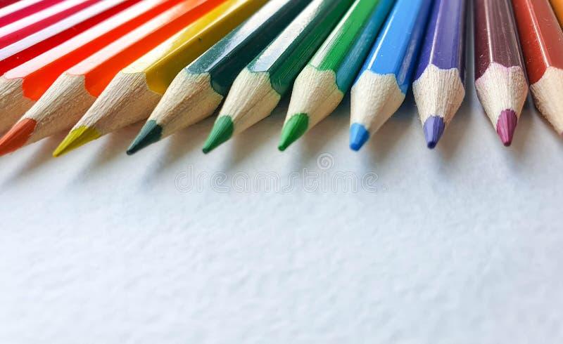 木色的铅笔,彩虹样式,在画纸白色板料与具体纹理的 r 免版税图库摄影