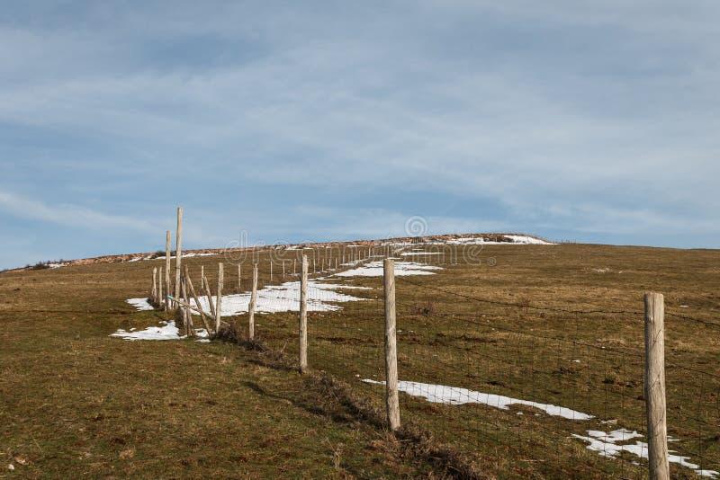 木表示一个雪大草原和补丁的地界线的有下干草的篱芭岗位和铁丝网  库存图片