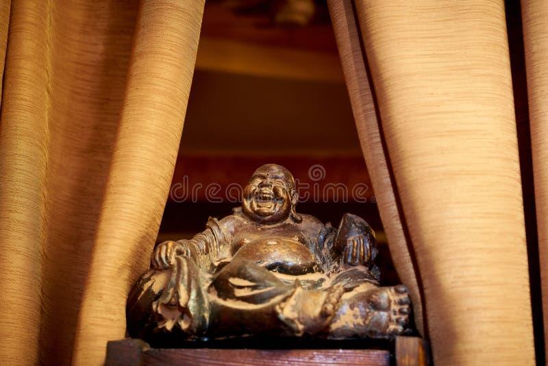 木表面上的一个老小雕象特写镜头在帷幕的边 由风水的护符Hotei是幸福, co的神 免版税库存照片