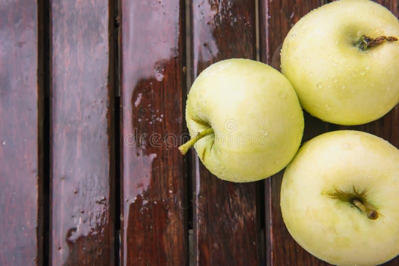木表面上的三个湿苹果 免版税图库摄影