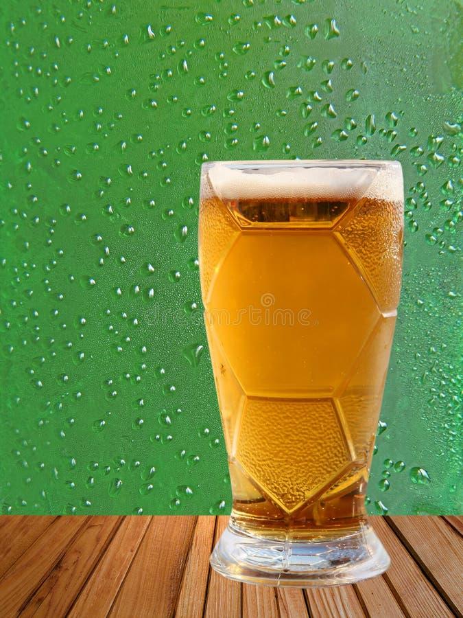 木表面上的啤酒杯反对滴水抽象背景 库存照片