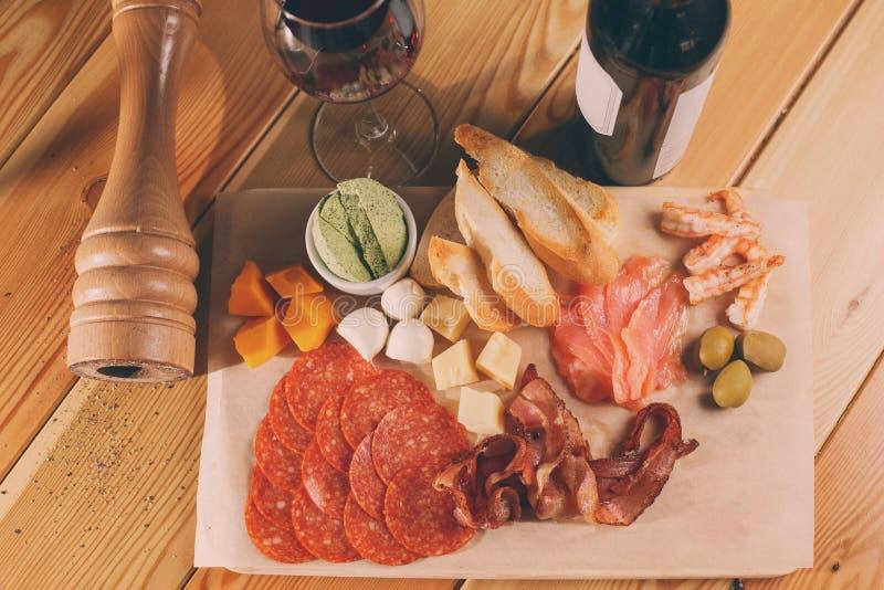 木表面上的开胃小菜盛肉盘 玻璃瓶酒 不同的快餐 库存照片