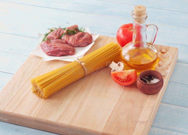 木表面上的意粉用蕃茄、蘑菇、肉和o 免版税库存照片