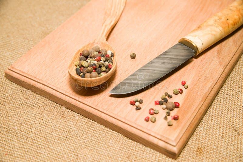 木表面上的猎刀、匙子和胡椒五谷 库存图片