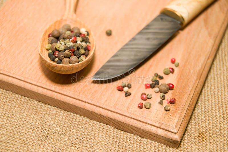 木表面上的猎刀、匙子和胡椒五谷 免版税图库摄影