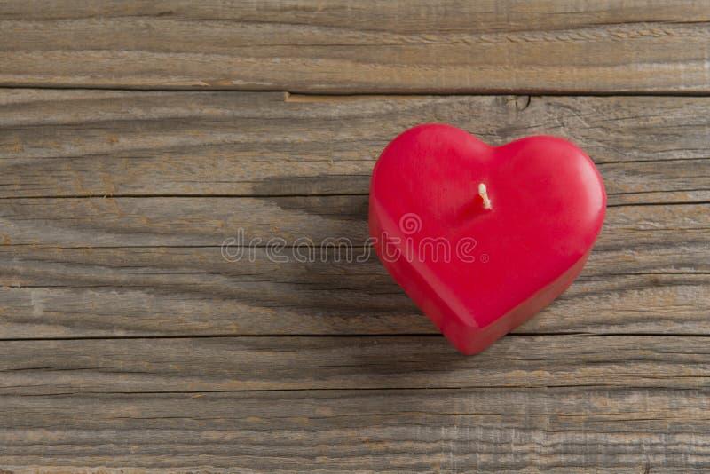 木表面上的红色心形的蜡烛 免版税库存照片
