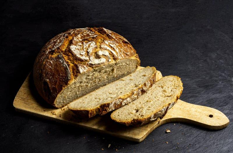 木表面上的被切的德国农夫面包baurenbrot有黑背景 库存图片