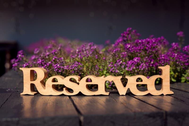 木被雕刻的后备的桌标志,桃红色花背景,木桌在室外餐馆 图库摄影