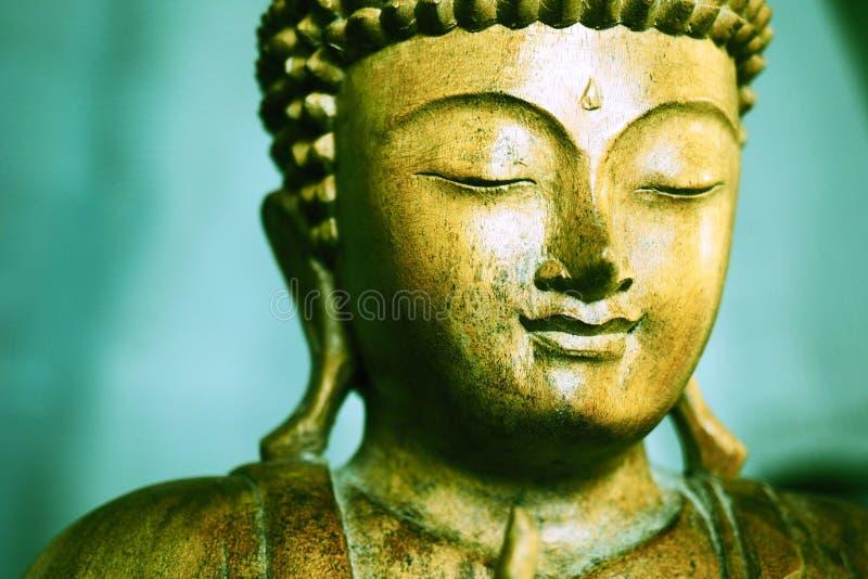 木被雕刻的菩萨面对有绿色背景 免版税库存图片